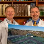 doctors posing with photo of rooftop solar panels